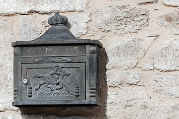 Rustic iron mailbox on a stone wall