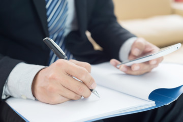 Image of businessman's hands laying on table with pen