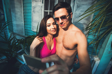Couple in love make fun and selfie at beach house on holiday