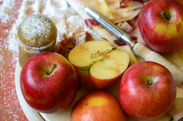 Sugar shaker, apples and peel knife on wooden chopping board