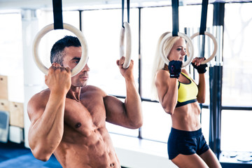 Man and woman workout on fitness rings
