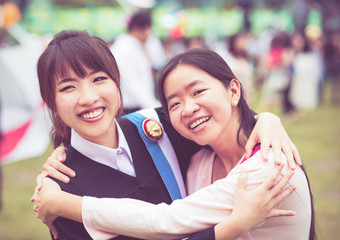 Thai girl is hugging her friend who graduated a master degree in