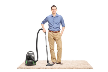 Young man posing next to a vacuum cleaner