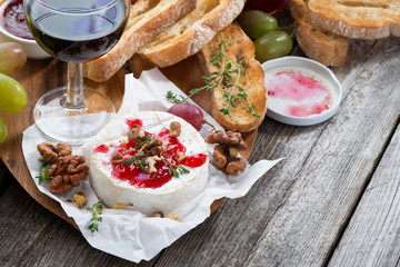 delicious appetizers - camembert with berry jam, toast and grape