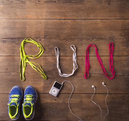 Shoelaces run sign, shoes and mp3 player on a wooden background