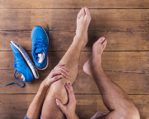 Unrecognizable injured runner sittin on wooden floor background