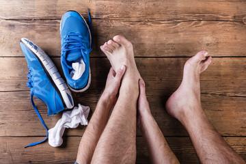 Unrecognizable injured runner sittin on wooden floor background