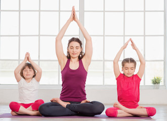 Young mother and daughters sitting in lotus position