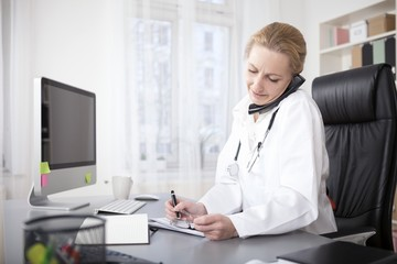 Physician Writing on Table While Talking on Phone