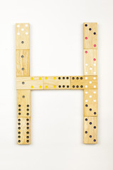 Alphabet letter H arranged from wood dominoes tiles isolated