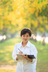 portrait of beautiful asian young woman staning in yellow flower