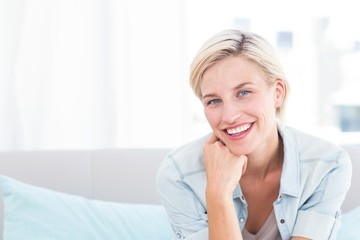 Pretty blonde woman sitting on the couch and smiling