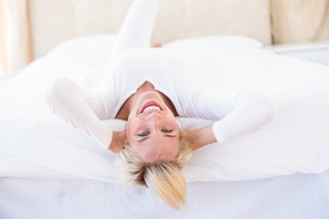 Smiling blonde woman lying on the bed