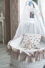 Retro interior children's bedroom with a wicker crib and teddy b