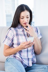 Shocked pretty brunette using smartphone on couch