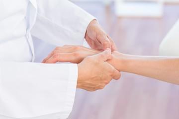 Doctor examining her patients wrist