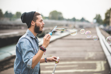 young handsome bearded hipster man blowing bubbles soap