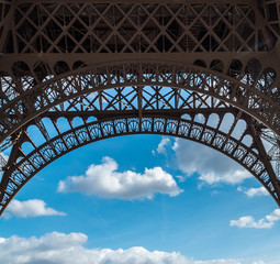 Eiffel tower closeup arch frame over blue cloudy sky