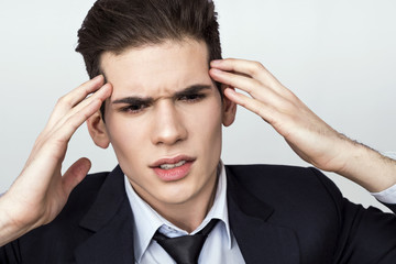 Young man in suit feeling headache