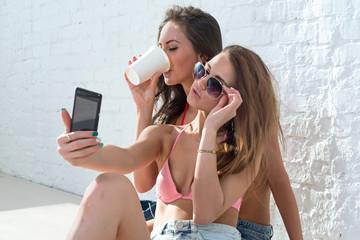 Female friends drinking coffee taking self-portrait picture