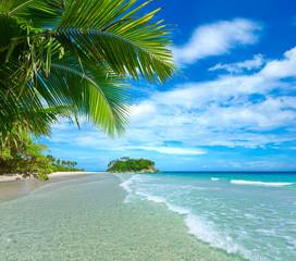 Naklejka premium Piękna tropikalna plaża z wyspą w tle