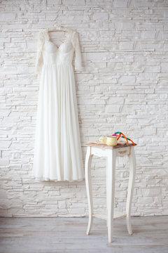 Beautiful wedding dress on hanger white brick wall