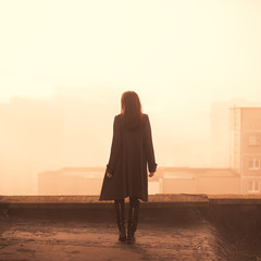 beautiful girl in a coat on a rooftop in the city. morning photo