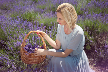 Young beautiful woman with a wicker basket in a lavender field
