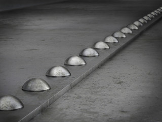 Row of rivets on the metal grunge background Leadership concept
