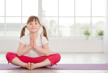 Smiling little girl in lotus position