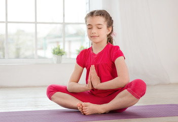 Little girl sitting in lotus position with closed eyes