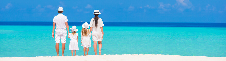 Rear view of young beautiful family on white tropical beach
