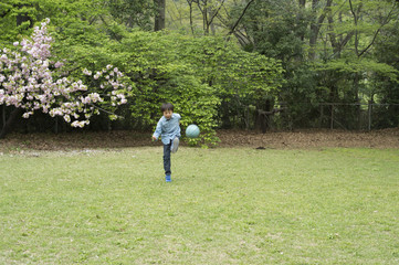 Boy playing with ball in green space
