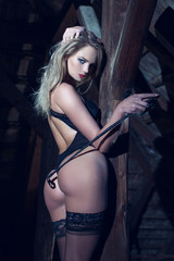 Sexy woman with leather whip posing at timber