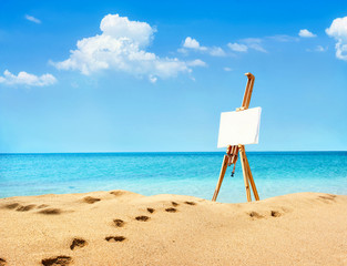 Beautiful landscape with easel on sandy beach