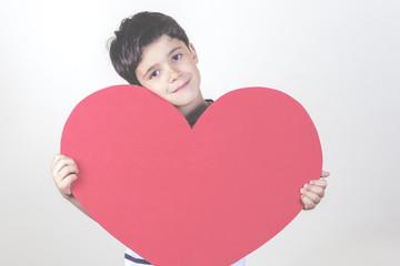 niño sonriente con un corazon rojo