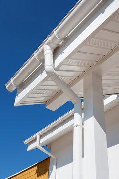New rain gutter on a white home against blue sky