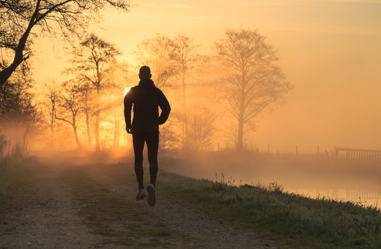 Trail runner during a foggy, spring sunrise in the countryside.