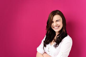 lachende junge frau vor rosa hintergrund