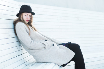 beautiful young girl in a hat sitting on a bench