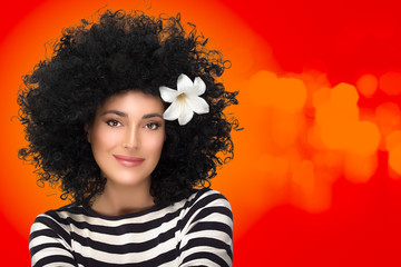 Beauty Fashion Brunette Girl with Flower in Curly Afro Hairstyle