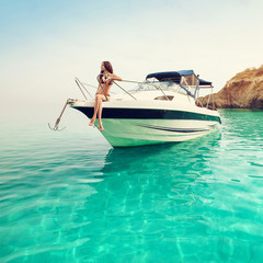 Beautiful young woman on boat. Luxury vacation at sea on yacht.