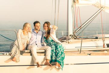 Young people taking selfie on exclusive luxury sailing boat
