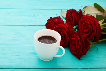 Cup of coffee with red roses on wooden background.Selective focus and top view