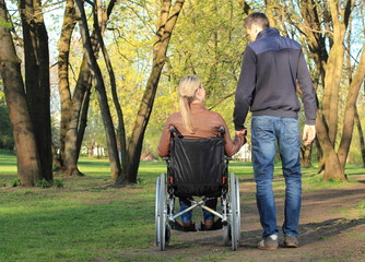 Pärchen Hand in Hand Rollstuhlfahrerin und Fußgänger