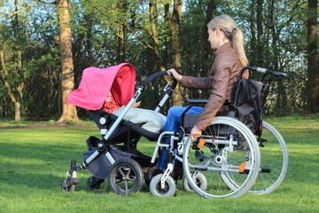 Mutter im Rollstuhl schiebt Kinderwagen im Park