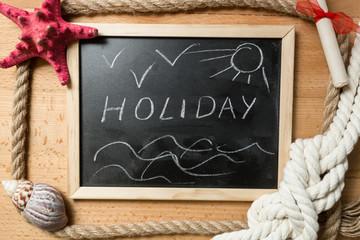 "Word ""Holiday"" written on blackboard decorated by seashells"