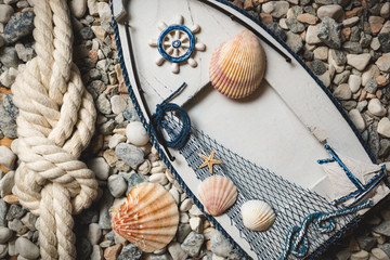 frame decorated by shells and ropes lying on stones at shore