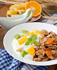 Healthy dessert with muesli and fruit in a white plate on the ta