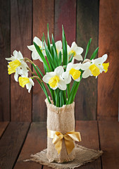 Bouquet of yellow narcissuses close up on a rustic wooden table